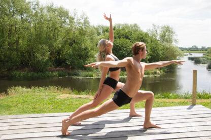 antybąkowa antybakteryjna bielizna na młodej kobiecie i młodym mężczyźnie, wspólnie ćwiczących jogę na drewnianym podeście nad jeziorem