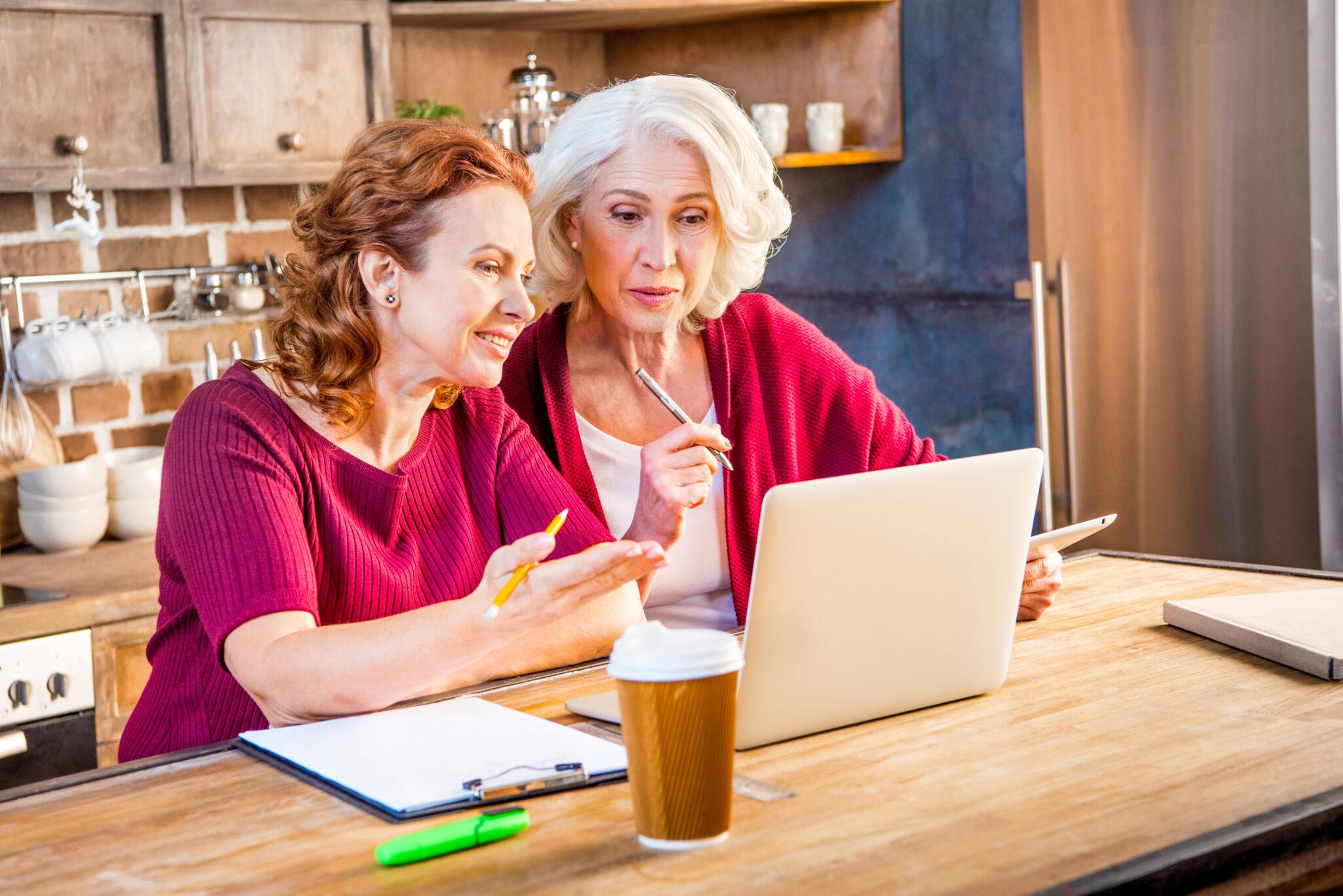 nietrzymanie moczu, poradnik - dwie kobiety w średnim wieku, jedna siwa, druga brązowowłosa, obie ładne i ubrane w czerwone sweterki, siedzą w kuchni przy stole, obok otwartego laptopa i szukają informacji na temat radzenia sobie z kontrolą nad pęcherzem